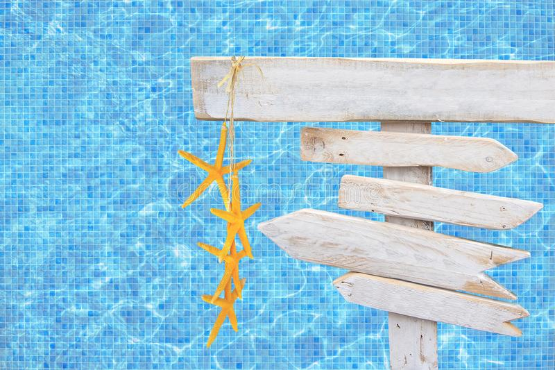 White rustic wood arrow signs with yellow starfish over turquoise blue mosaic pool water royalty free stock images