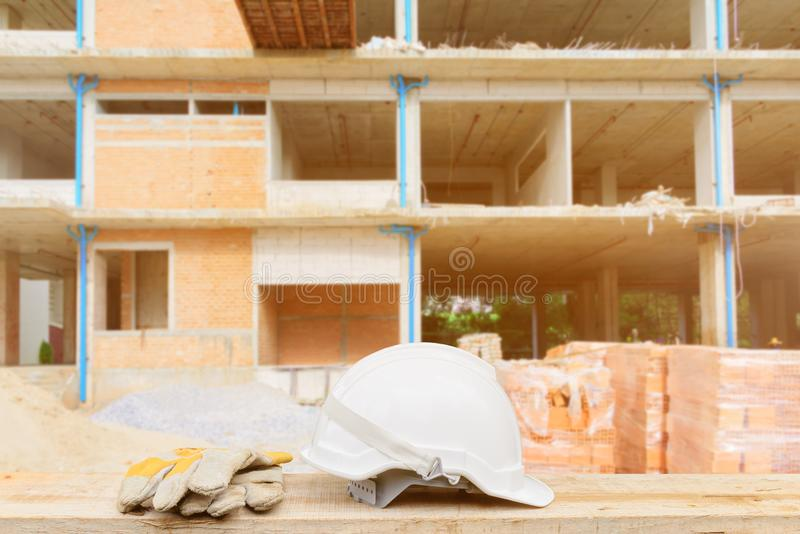White safety helmet and leather glove for engineering working construction site building on wood. Floor table with copy space. blur background royalty free stock photos