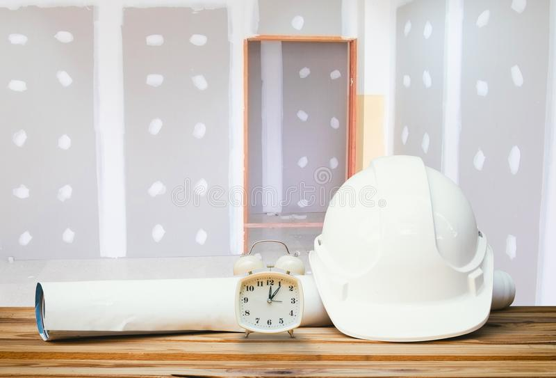 White safety helmet plastic, paper roll plan blueprint alarm clowhite safety helmet plastic, paper roll plan blueprint alarm clock. White safety helmet plastic royalty free stock photos