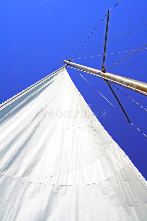 White sail. Down shot photo for a full white sail with no wind. Background the clear blue sky royalty free stock image