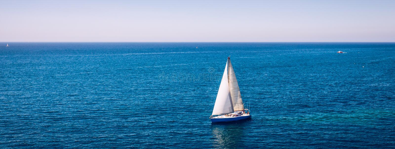 White sail boat isolated in blue sea water. Sailboat in the sea in the sunlight, luxury summer adventure, active vacation in royalty free stock photos