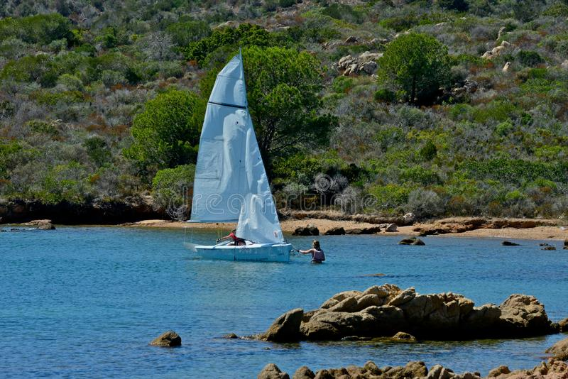 White sail boats with two people learning to sail in the blue sea surrounded by nature stock photography