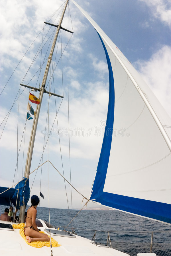 White sail and cloudy sky. White sail, cloudy sky and women on the yellow towel on the yacht royalty free stock photos
