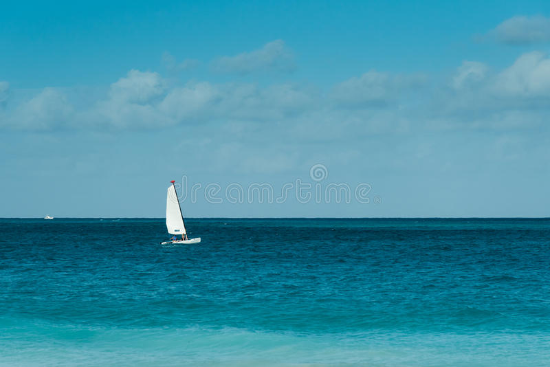 White sail. Couple on hobby cat under white sail browsing ocean royalty free stock photo