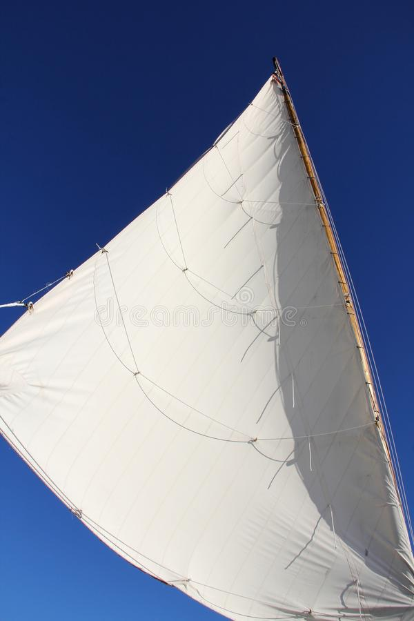 White sail of a sailboat in the sky. A picture of a white sail of a sailboat in the sky in the summer royalty free stock images