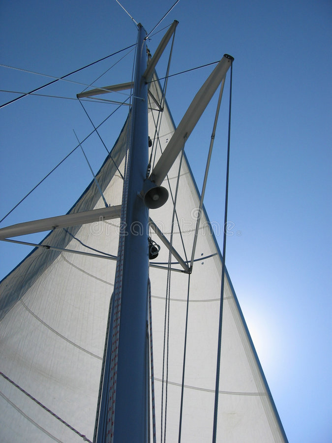 White sail and yacht mast. White sail against sun lit blue sky royalty free stock image