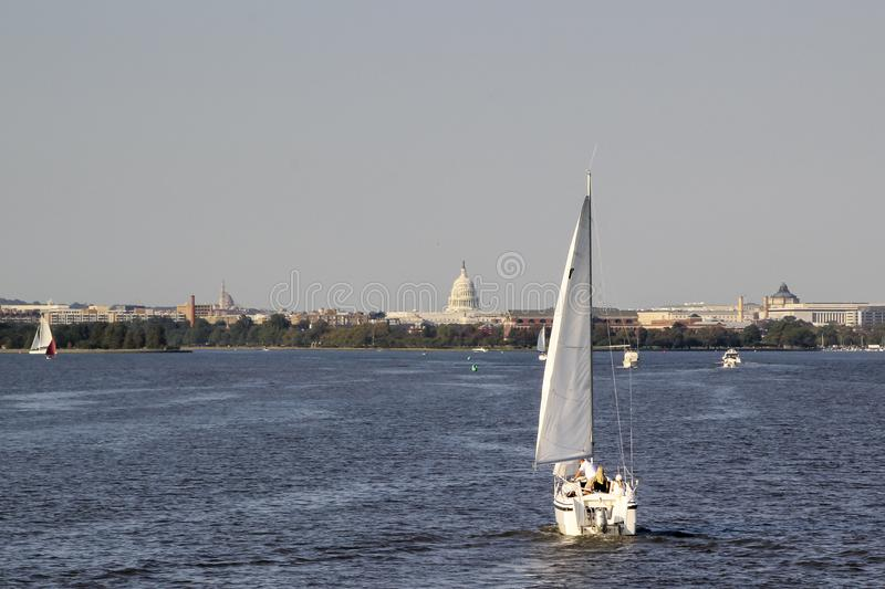White sailboat on the Potomac River with the Capitol building in the background stock photo
