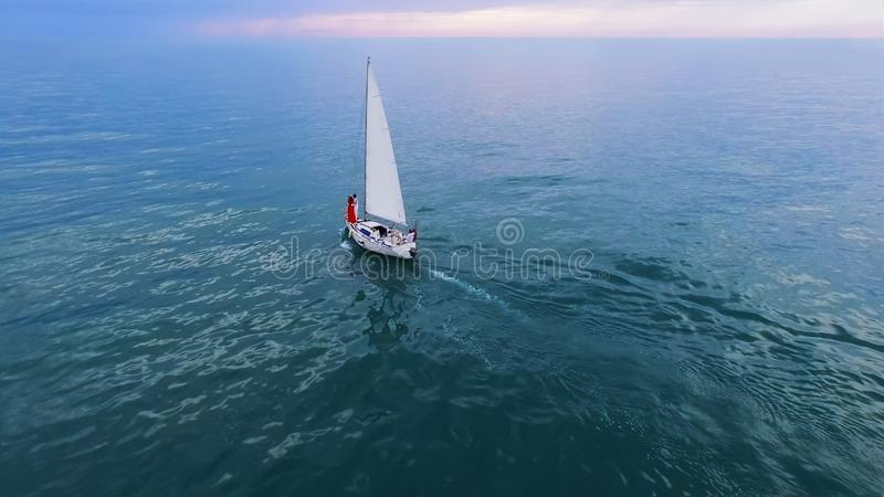 White sailing boat with couple at sea, romantic cruising leisure, freedom stock image