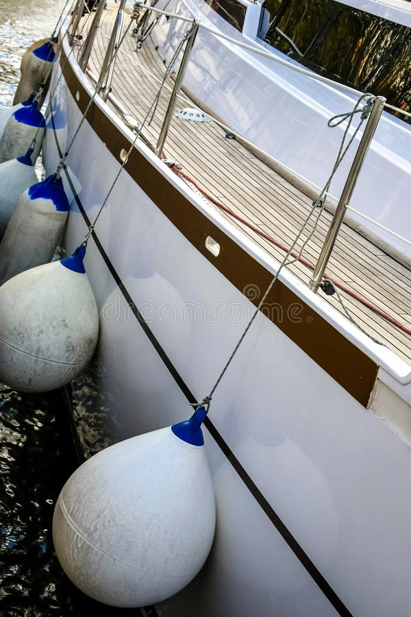 White sailing yacht moored in the port. Protective buoys hanging from the side of the ship. Close-up royalty free stock photography
