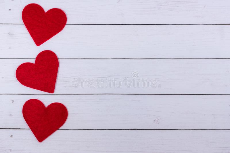 White Saint Valentine`s day background with three red hearts, copy space royalty free stock image