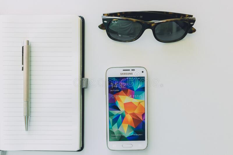 White Samsung Smartphone Beside Sunglasses,pen and White Notebook stock photography