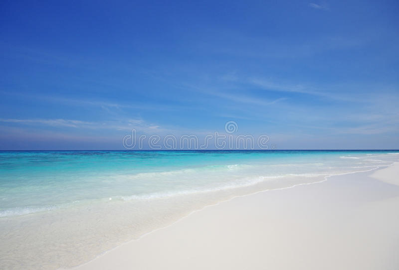 White sand beach and blue sky stock photography