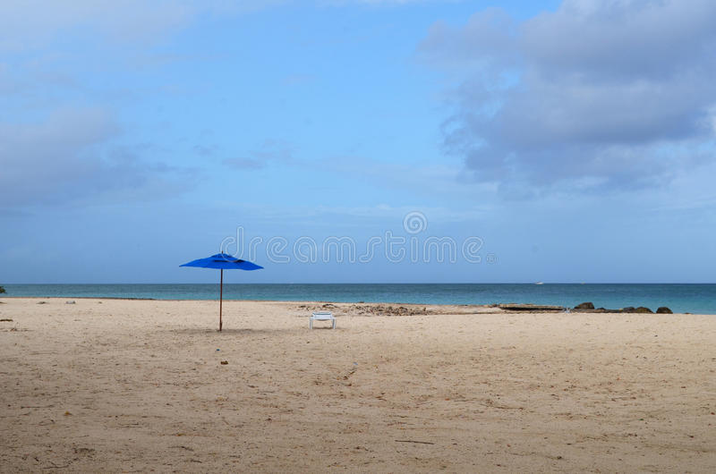 Blue Umbrellas Standing Alone on a White Sand Beach. White sand beach with a blue umbrella standing alone stock photos