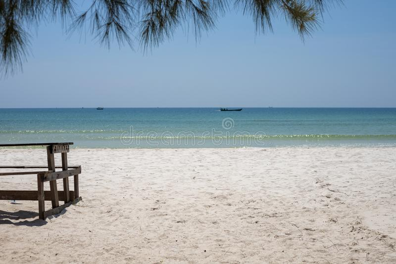 White sand beach with rustic wooden bench and table. Tropical island in South Asia. Turquoise blue sea landscape. royalty free stock photography
