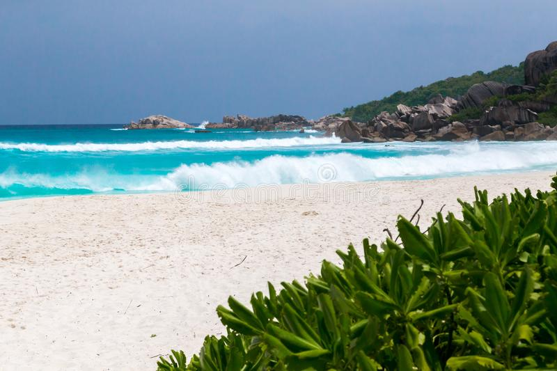 A white sand beach with turqouise water and stones stock images