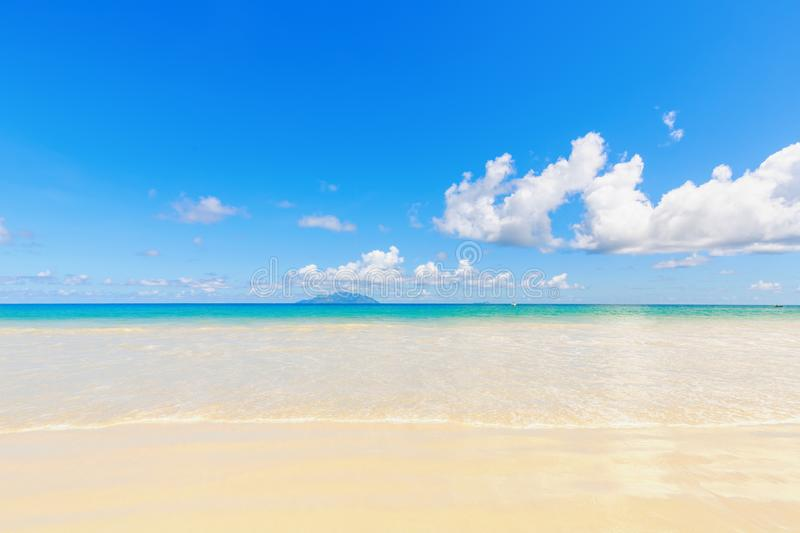 White sand tropical beach with far view of island and blue sky stock photography