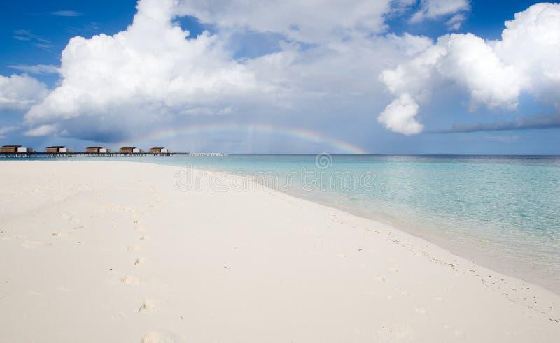 White sandy beach and rainbow stock photography