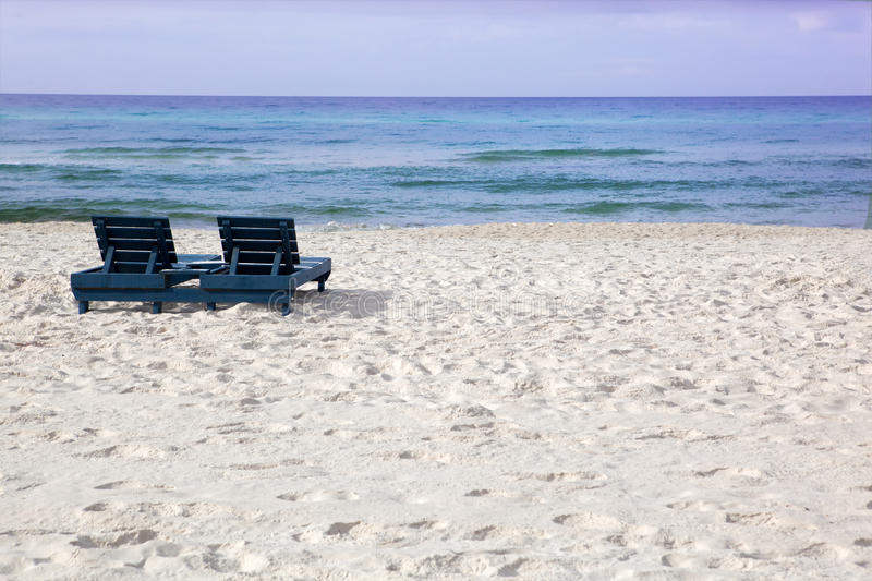 White sandy beach viewing the ocean with empty lou royalty free stock photo