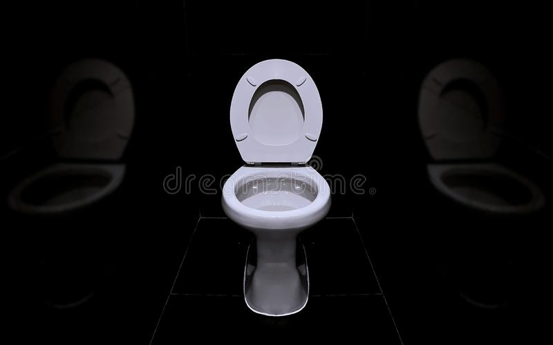 A white sanitary ware in a dark toilet room. With blur reflect stock photo