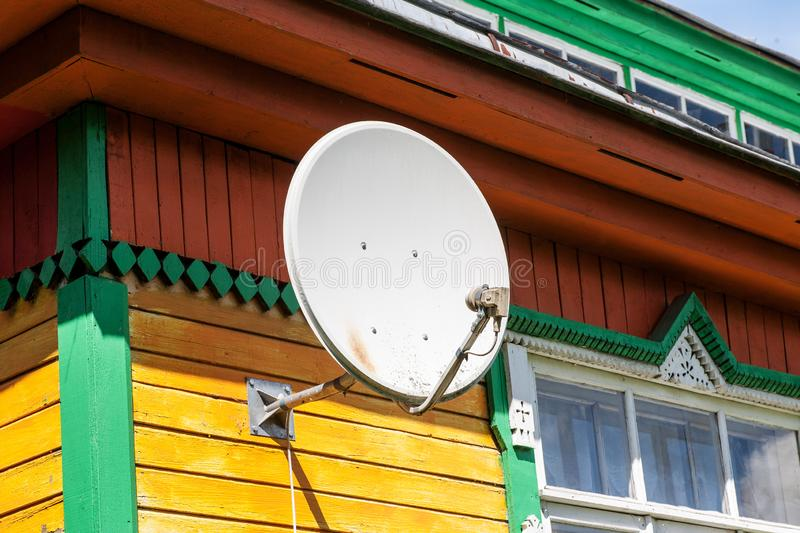 White satellite dish on a colored wall of village house.  stock photos