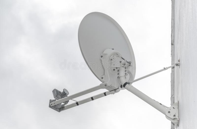 Satellite dish on a wall. White satellite dish mounted to the wall on a building royalty free stock photo