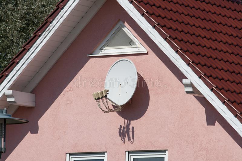 Satellite dish on a wall stock images
