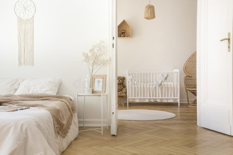 White scandinavian bedroom with door open to nursery. With crib and toys, real photo royalty free stock images