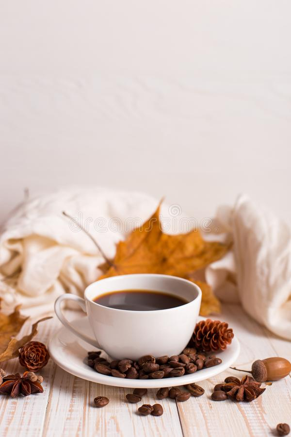 White scarf, a cup of coffee with scattered coffee beans, dry yellow leaves on a wooden table. Autumn mood, copy space royalty free stock photo