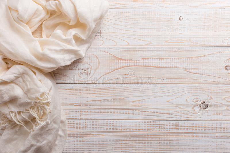 White scarf on a wooden table. Autumn background, copy space royalty free stock photo
