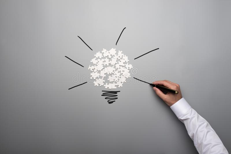 Scattered puzzle pieces and male hand drawing light bulb royalty free stock photo