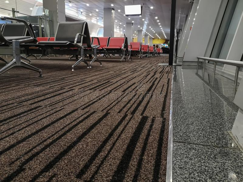 A white screen hangs from the ceiling above an empty waiting room at the station or at the airport. Hall with rows of seats, royalty free stock image
