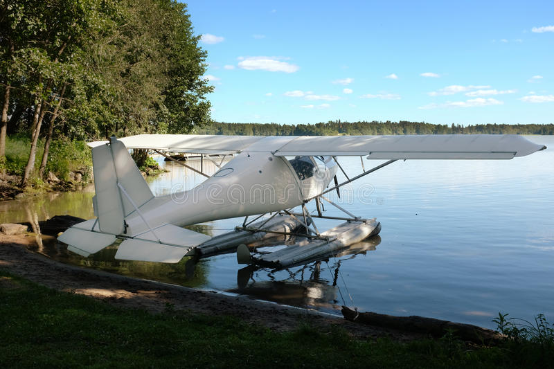 White seaplane on the lake shore. In summer royalty free stock photography