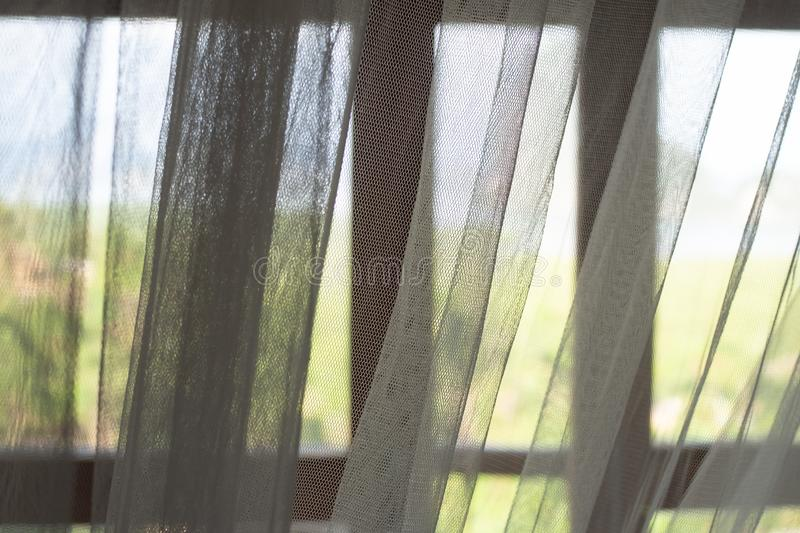 White see through curtains with blurred window frame and natural mountain and green tree outdoor view. Calm and relax on vacation concept royalty free stock photography
