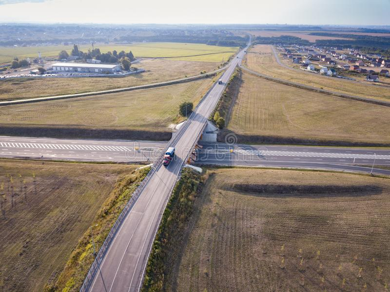 White Semi Truck with Cargo Trailer Passing Highway Overpass. 18 Wheeler car on road, drive towards Loading Warehouses. Aerial royalty free stock images