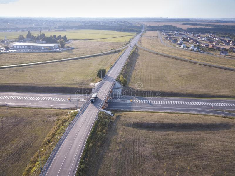 White Semi Truck with Cargo Trailer Passing Highway Overpass. 18 Wheeler car on road, drive towards Loading Warehouses. Aerial. View stock photography