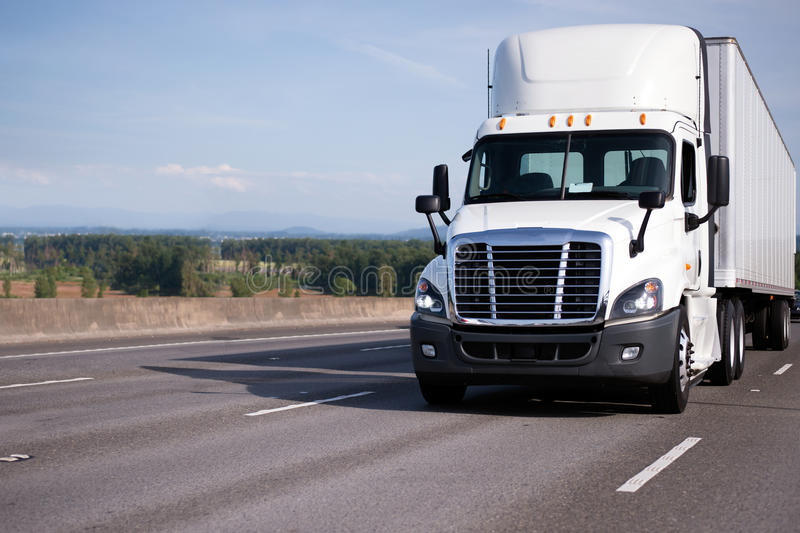 White semi truck with high roof day cab and semi trailer move on royalty free stock photography