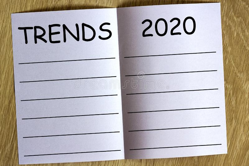 White sheen of paper on wooden background with text. `Trends 2020` on it royalty free stock photos