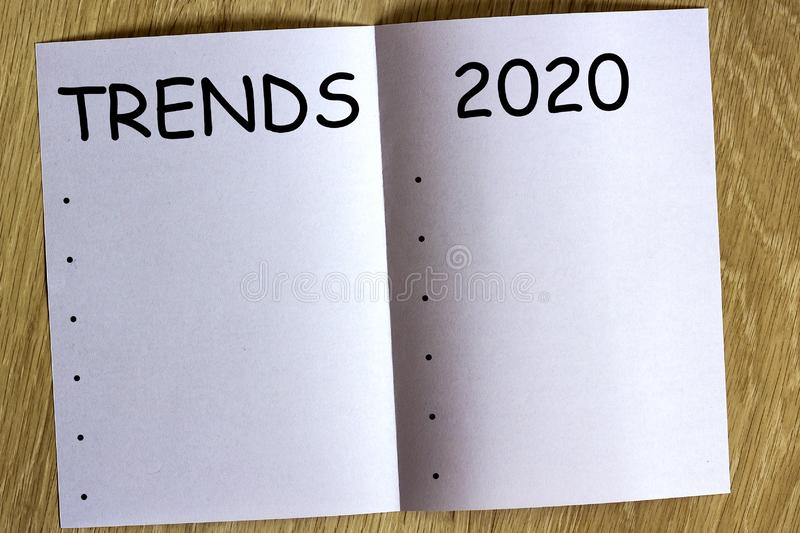 White sheen of paper on wooden background with text. `Trends 2020 ` on it royalty free stock photo