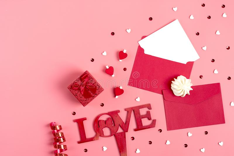 A white sheet of paper for message to loved one, red envelope, gift box, tittle sparkles,word love from black letters pen on pink stock image