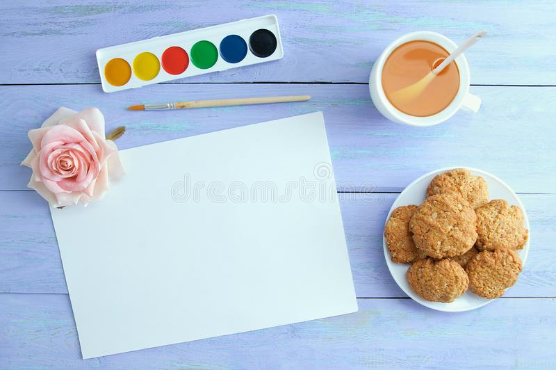 White sheet of paper, watercolors, green tea in a cup and cookies. stock image