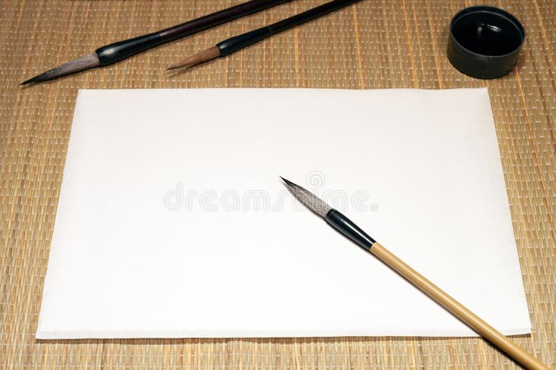 White sheet of washi paper, chinese brushes and inkwell on cane matting background. White empty sheet of washi paper, chinese bamboo calligraphy brushes and stock photo