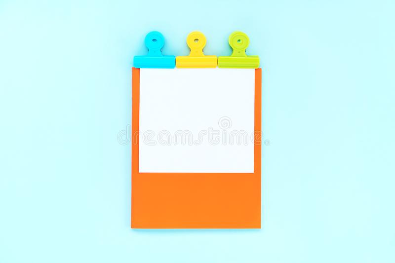 A white sheet for writing on an orange notebook. Attached by three multi-colored stationery clips. Concept back to school. Minimalism flat lay stock photo