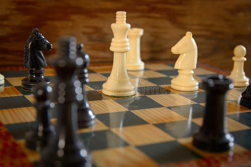 White sheets against blacks on chessboard. Close-up of a chess game in which Black checks the white king strategy success concept board business competition stock photo
