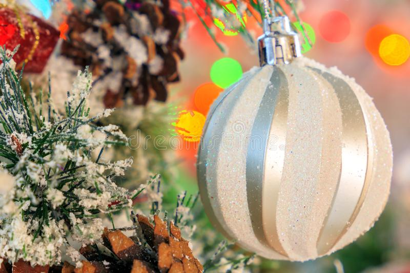 White shiny ball hanging on a snow-covered branch of a Christmas tree against a backdrop of multicolored lights stock image