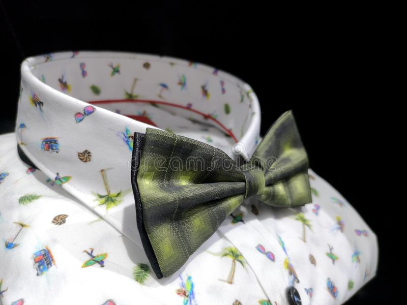 White shirt with bright summer patterns with a beautiful green bow tie royalty free stock photo