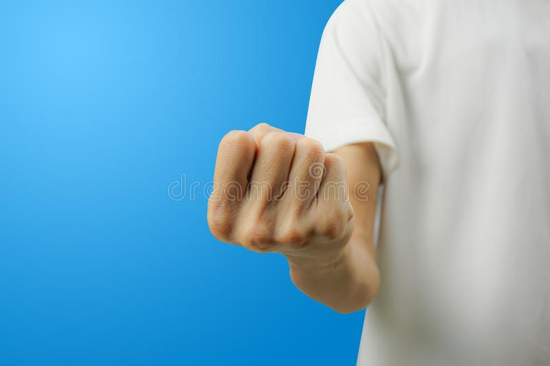 A white shirt man showing fist with his hand front view on blue background. Carefully cut out by pen tool and insert clipping path stock photography