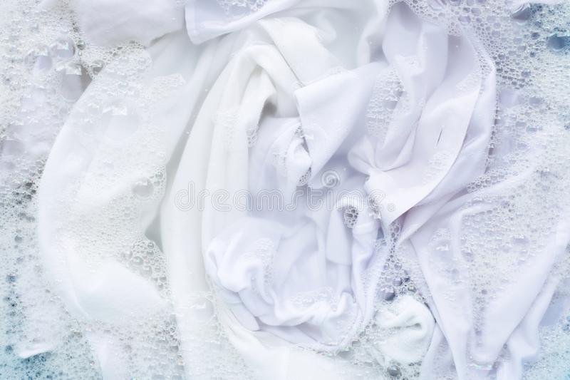 White shirt soak in powder detergent water dissolution. Laundry concept stock photography