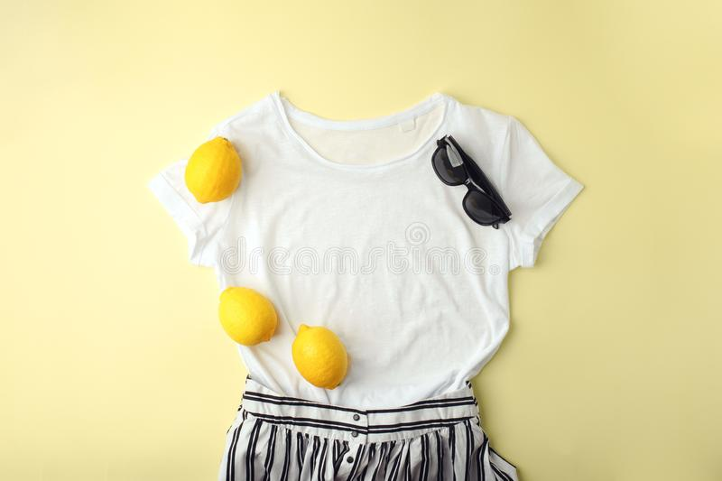 White shirt, sunglasses and lemons on yellow background. Women`s stylish spring summer outfit. Trendy clothes. Flat lay, top view stock image