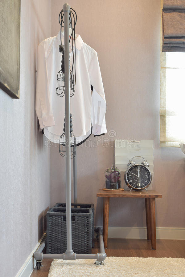 White shirts hanging on standing rail and decorative alarm clock stock photos