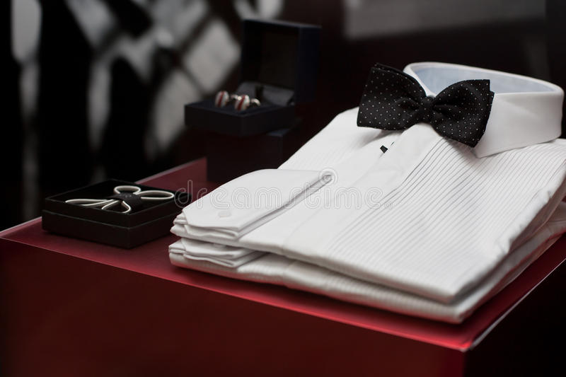 WHITE SHIRTS FOR SALE IN A WINDOW DISPLAY. White luxury mens shirts with bow tie, in a window display stock photos